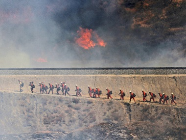 A fire crew approaches as a wildfire burns in California. AP