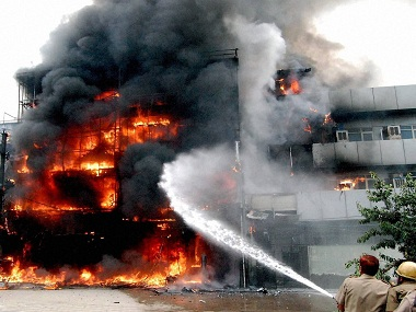 New Delhi: Firefighters dousing a fire that broke out in a commercial building destroying a number of motorcycles in Mahindra Enclave in New Delhi on Tuesday. PTI Photo (PTI8_23_2016_000342B)