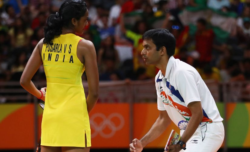 Sindhu deep in conversation with coach Pullela Gopichand at the end of game 2. Getty