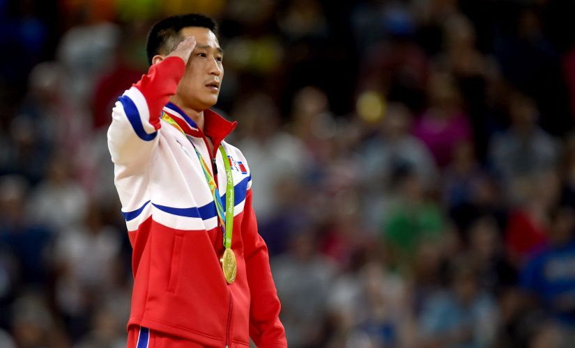 Gold medalist Se Gwang Ri of North Korea salutes on the podium at the medal ceremony. Getty