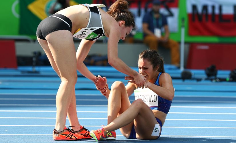 Abbey D'Agostino assisted by Nikki Hamblin after a collision. Getty