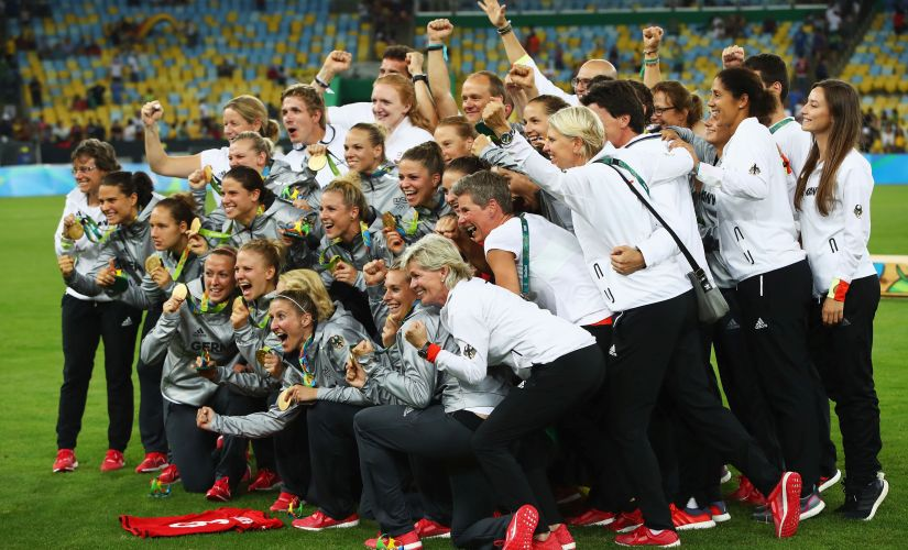 German players celebrate as they receive their medals following victory in the Women's Olympic Gold Medal. Getty