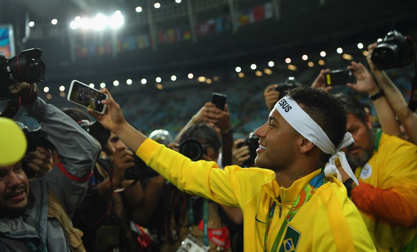 Neymar takes a selfie with a fans camera after winning gold in the Men's Football Final. Getty