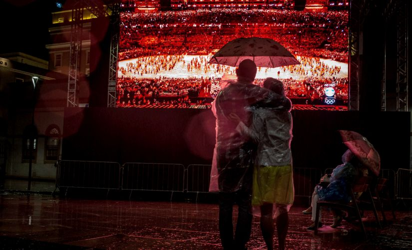 People watch the Rio 2016 Olympics closing ceremony in the rain at the Olympic Boulevard live site. Getty