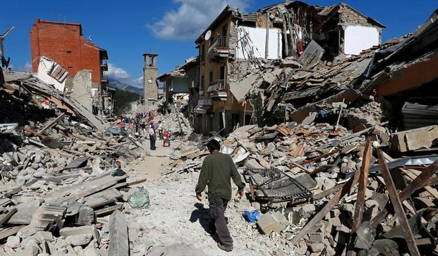 A man walks amidst rubble following an earthquake in Pescara del Tronto, central Italy. Reuters
