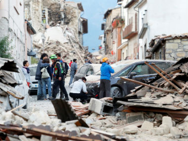 People stand along a road following a quake in Amatrice, central Italy. Reuters