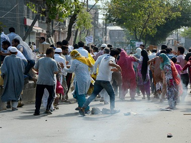 Srinagar: Protesters runs for cover amid tear gas smoke fired by police to disperse them during clashes in Srinagar on Wednesday. PTI Photo (PTI8_24_2016_000232B)