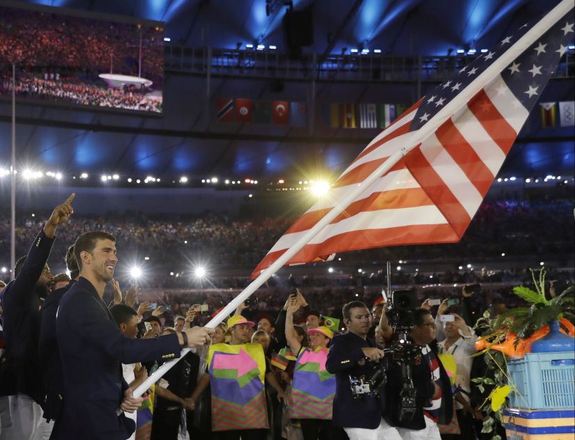 Michael Phelps carries the USA flag at Rio 2016. AP