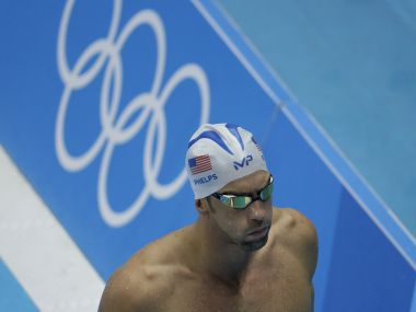 Michael Phelps walks past the Olympic rings during a swimming training session. AP