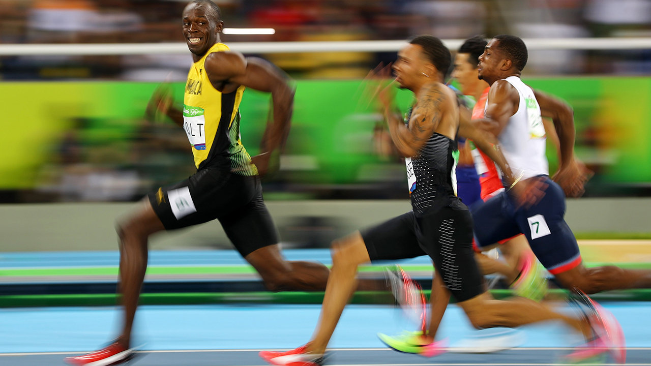 2016 Rio Olympics - Athletics - Semifinal - Men's 100m Semifinals - Olympic Stadium - Rio de Janeiro, Brazil - 14/08/2016. Usain Bolt (JAM) of Jamaica looks at Andre De Grasse (CAN) of Canada as they compete. REUTERS