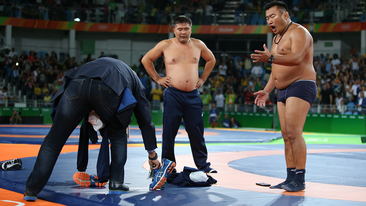 2016 Rio Olympics - Wrestling - Final - Men's Freestyle 65 kg Bronze - Carioca Arena 2 - Rio de Janeiro, Brazil - 21/08/2016. The coach (R) of Mandakhnaran Ganzorig (MGL) of Mongolia stands undressed as he protests after the match against Ikhtiyor Navruzov (UZB) of Uzbekistan. REUTERS