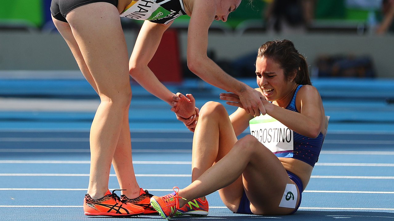 2016 Rio Olympics - Athletics - Preliminary - Round 1 - Olympic Stadium - Rio de Janeiro, Brazil - 16/08/2016. Nikki Hamblin (NZL) of New Zealand stops running during the race to help fellow competitor Abbey D'Agostino (USA) of USA after D'Agostino suffered a cramp. REUTERS