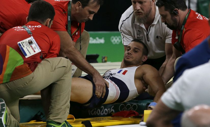 Samir Ait Said is assisted after injuring his leg in the vault during the artistic gymnastics men's qualification. AP
