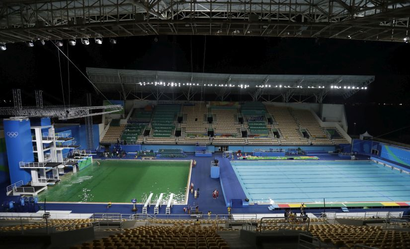 The water of the diving pool appears a murky green, in stark contrast to the pool's previous day's color. AP