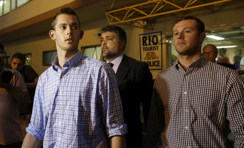 American Olympic swimmers Gunnar Bentz and Jack Conger leave a police station.The two were taken off their flight from Brazil to the US by authorities amid an investigation into a reported robbery. AP