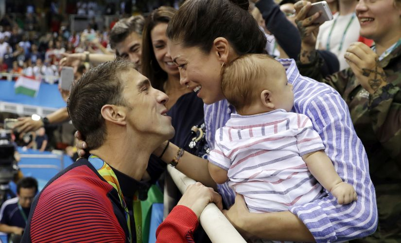 Michael Phelps celebrates winning his gold medal in the men's 200-meter butterfly with his fiance Nicole Johnson and baby Boomer. AP