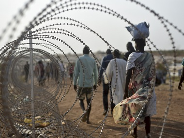 FILE- In this file photo taken Tuesday, Jan. 19, 2016, displaced people walk next to a razor wire fence at the United Nations base in the capital Juba, South Sudan. South Sudanese government soldiers raped dozens of ethnic Nuer women and girls last week just outside a United Nations camp where they had sought protection from renewed fighting, and at least two died from their injuries, witnesses and civilian leaders said. The rapes in the capital of Juba highlighted two persistent problems in the chaotic country engulfed by civil war: targeted ethnic violence and the reluctance by U.N. peacekeepers to protect civilians. (AP Photo/Jason Patinkin, File)