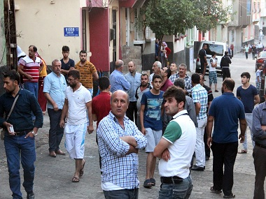 """People gather to view damage just hours after Saturday's bomb attack in Gaziantep, southeastern Turkey, early Sunday, Aug. 21, 2016, targeting an outdoor wedding party in southeastern Turkey killed dozens of people and wounded dozens. Deputy Prime Minister Mehmet Simsek said the """"barbaric"""" attack in Gaziantep, near the border with Syria, on Saturday appeared to be a suicide bombing. Turkish authorities have put a temporary ban on distribution of images relating to Saturday's Gaziantep attack within Turkey. (IHA via AP)"""