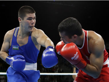 Vikas Krishan (left) receives a blow from his Uzbek opponent Bektemir Melikuziev. AP