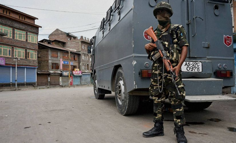 An Indian Army soldier stands guard in curfew-hit part of Kashmir. PTI