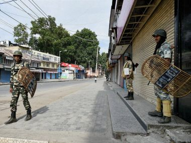 Security jawans stand guard as tension prevails in Srinagar on Sunday. PTI