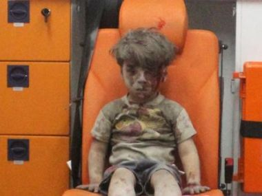 Five-year-old Omran Daqneesh, with bloodied face, sits inside an ambulance after he was rescued. Reuters