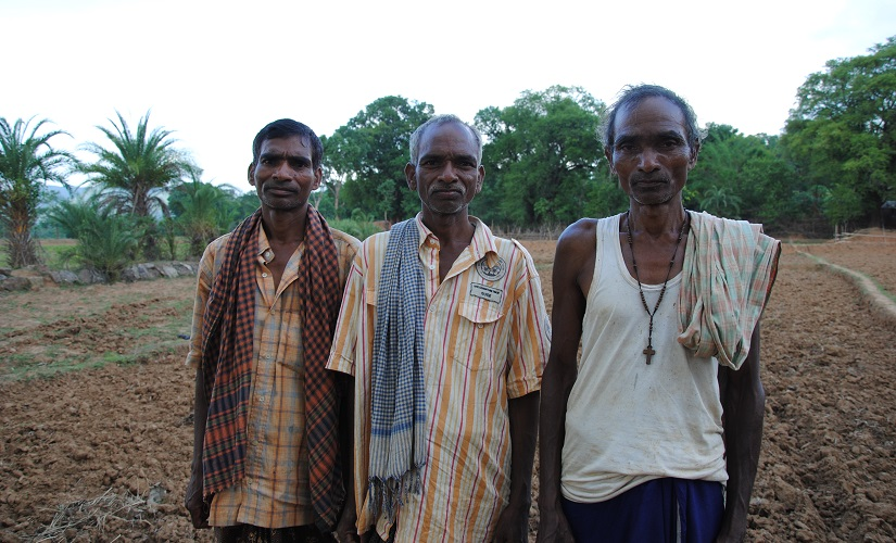 Julian Pradhan (extreme right), with his two brothers on the land they own. Firstpost/Rahul Pandita