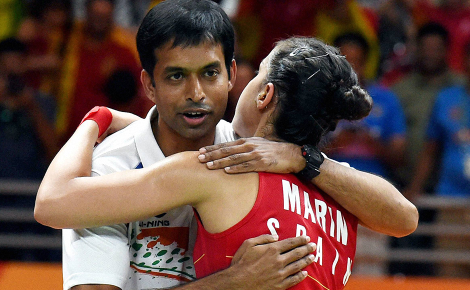 Rio de Janeiro:Spain's Carolina Marin with Indian coach Pullela Gopichand after defeating India's V. Sindhu Pusarla in the women's badminton singles gold medal match at the 2016 Summer Olympics at Rio de Janeiro in Brazil on Friday. PTI Photo by Atul Yadav (PTI8_19_2016_000337B)