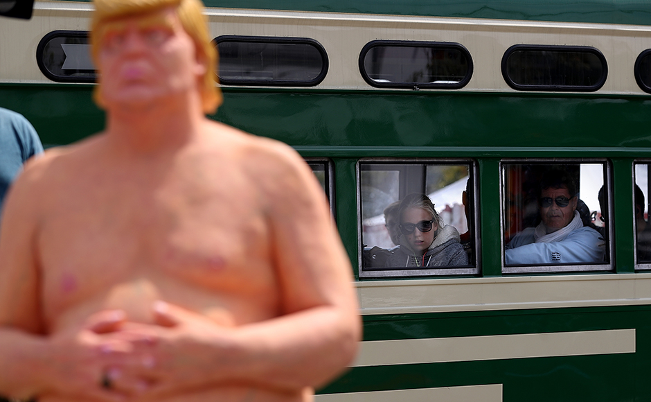SAN FRANCISCO, CA - AUGUST 18: Train passengers look at a statue depicting republican presidential nominee Donald Trump in the nude on August 18, 2016 in San Francisco, United States. Anarchist collective INDECLINE has created five statues depicting Donald Trump in the nude and placed them in five U.S. cities on Thursday morning. The statues are in San Francisco, New York, Los Angeles, Cleveland and Seattle. (Photo by Justin Sullivan/Getty Images)