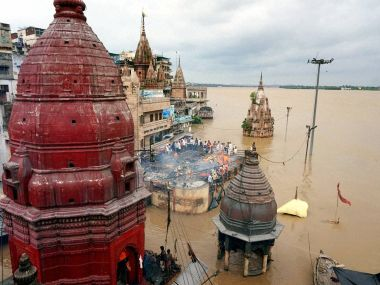 Cremations being performed on the roof a building as the famous Manikarnika Ghat is seen flooded in Varanasi on Monday. PTI