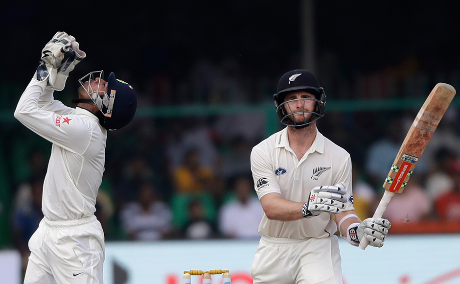 Indian wicket-keeper Wriddhiman Saha, left, reacts after New Zealand's captain Kane Williamson hits a shot on the second day of their cricket test match at Green Park Stadium in Kanpur, India, Friday, Sept. 23, 2016.AP