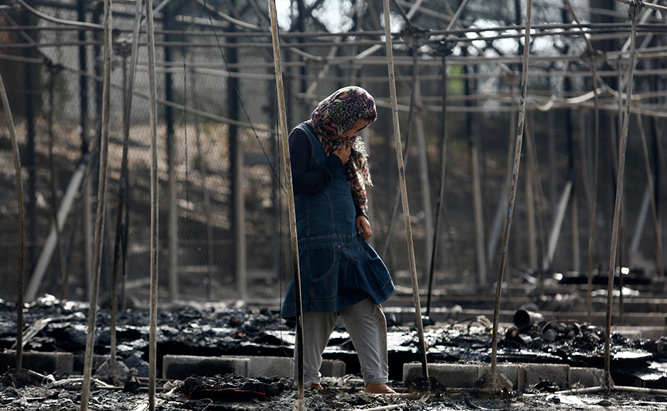 A migrant stands amid the burned remains of a tent at the camp. Refugees and migrants on Lesbos are stranded by a European Union deal with Turkey preventing them going beyond the island until their asylum claims have been processed. Reuters