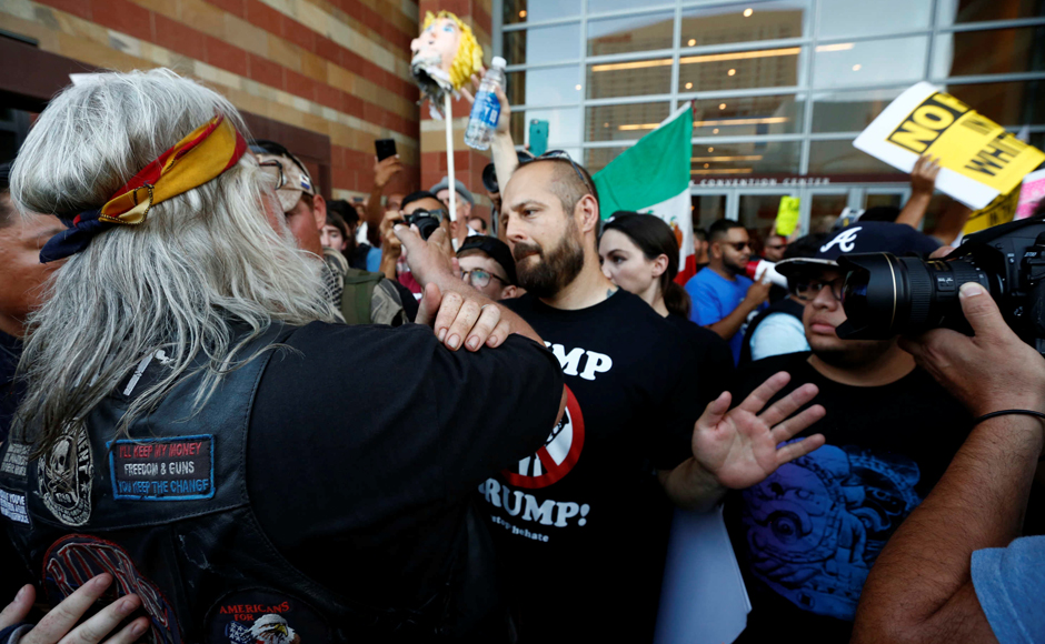 A man faces off with protesters during a rally against Donald Trump in Phoenix, Arizona. REUTERS