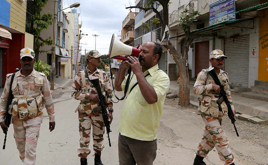 Uneasy calm prevailed in violence-hit Bengaluru on Tuesday even as protests resumed at Mandya and Mysuru in southern Karnataka over releasing more Cauvery river water to Tamil Nadu. An Indian policeman in plain clothes makes an announcement asking people to stay indoors during curfew in Bangalore. (Photo: AP)