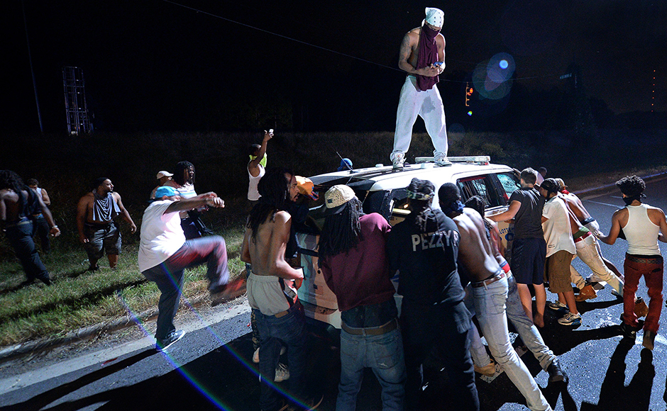 Protesters surround a police vehicle in Charlottent complex. Police in riot gear reportedly used tear gas on protesters who threw rocks and water bottles at them as they wielded large sticks and blocked traffic. AP