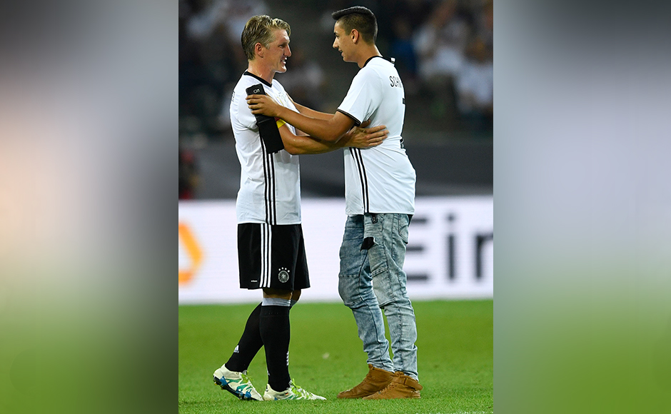 Germany's Bastian Schweinsteiger talks to a fan who jumped on the pitch during a friendly soccer match between Germany and Finland in Moenchengladbach, Germany, Wednesday, Aug. 31, 2016.AP