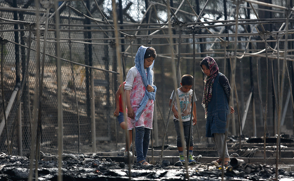 Migrants stand among the remains of a burned tent at the Moria migrant camp. At least nine people were arrested on accusations of damaging property and causing unrest and were expected to appear before a prosecutor, a police official in Athens said.REUTERS