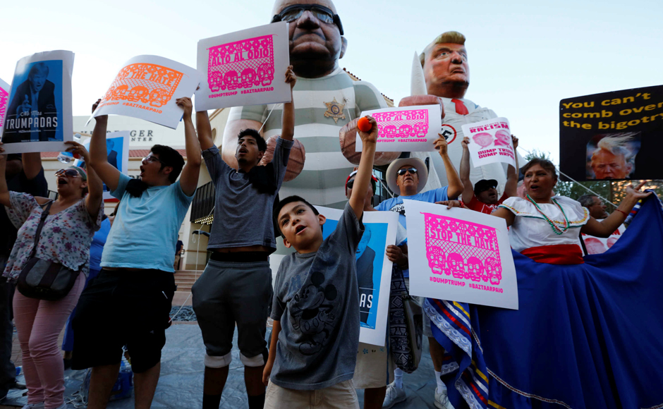 Protesters rally against Donald Trump, who is in town to speak on immigration, in Phoenix, Arizona. REUTERS