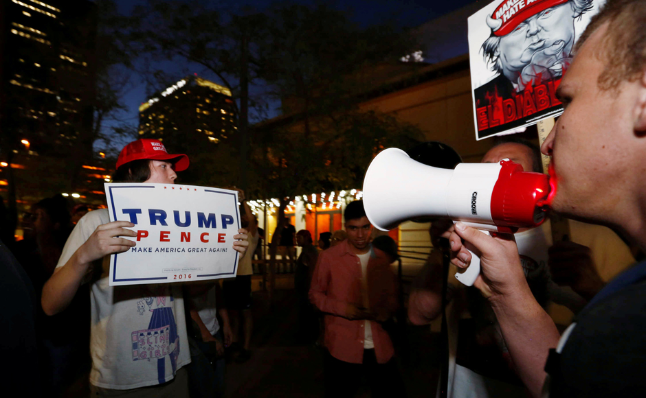 Protesters face off with a supporter of Donald Trump outside the Phoenix Convention Center as the candidate gives a speech on immigration in Phoenix, Arizona. REUTERS