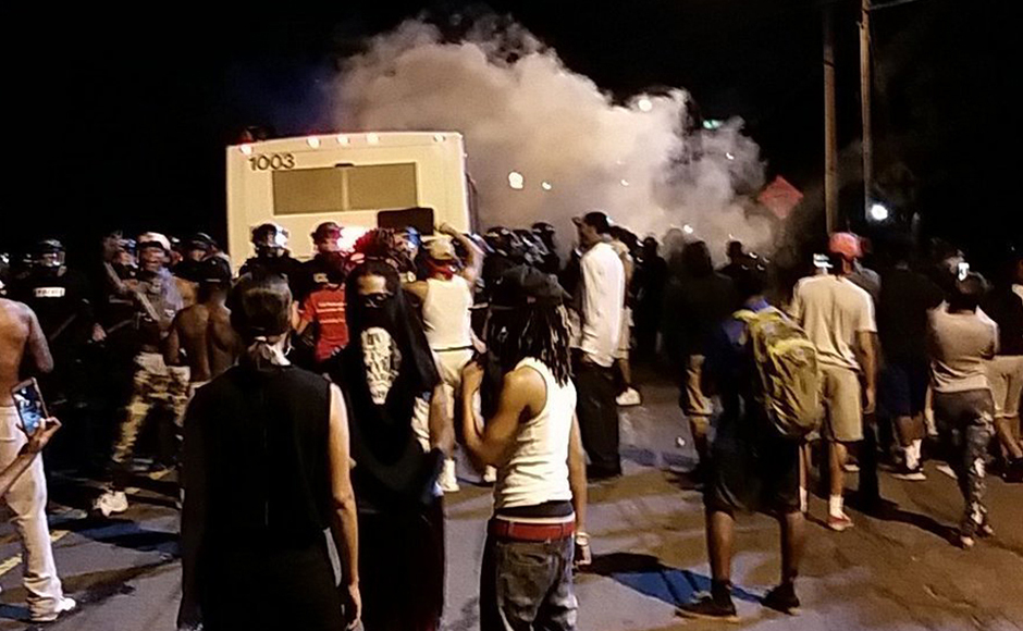 Police fire tear gas into the crowd of protesters on Old Concord Road late Tuesday night, Sept. 20, 2016, in Charlotte, N.C. A black police officer shot an armed black man at an apartment complex Tuesday, authorities said, prompting angry street protests late into the night. The Charlotte-Mecklenburg Police Department tweeted that demonstrators were destroying marked police vehicles and that approximately 12 officers had been injured, including one who was hit in the face with a rock.AP