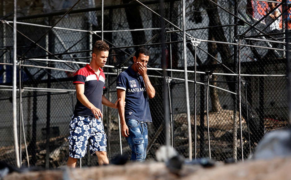 A migrant (R) reacts as he walks next to the remains of burned tents at the Moria migrant camp. Thousands have applied for asylum and the wait is long, ranging from weeks to months. Just over 500 people have been deported to Turkey since March but none of those who have requested asylum were among those, Greece says.REUTERS