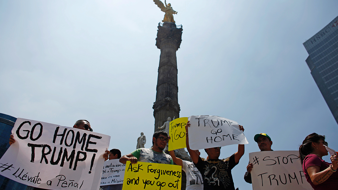 Demonstrators hold placards during a protest against the visit of U.S. Republican presidential candidate Donald Trump, at the Angel of Independence monument in Mexico City, Mexico, August 31, 2016. REUTERS