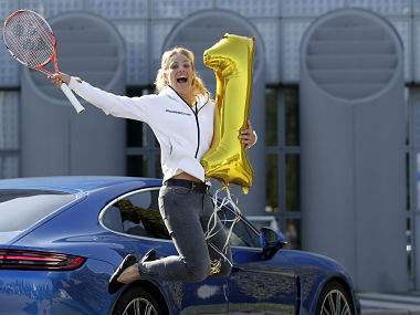 Germany's Angelique Kerber jumps as she poses for photographers after her arrival in Munich, Germany. AP