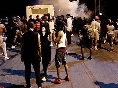 Police fire tear gas into the crowd of protesters on in Charlotte, NC. A black police officer shot an armed black man at an apartment complex Tuesday, authorities said, prompting angry street protests late into the night. The Charlotte-Mecklenburg Police Department tweeted that demonstrators were destroying marked police vehicles and that approximately 12 officers had been injured, including one who was hit in the face with a rock. AP