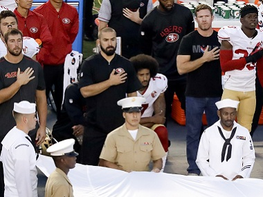 San Francisco 49ers quarterback Colin Kaepernick (centre) kneels during the national anthem. AP