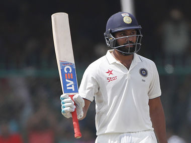India's Rohit Sharma raises bat after scoring fifty runs on the fourth day of their first cricket test match against New Zealand at Green Park Stadium in Kanpur, India, Sunday, Sept. 25, 2016. (AP Photo/ Tsering Topgyal)