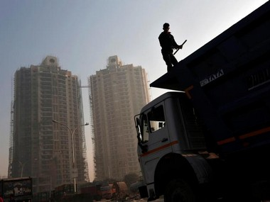 A labourer stands on a truck carrying construction materials at a construction site of residential buildings in Noida on the outskirts of New Delhi.  REUTERS