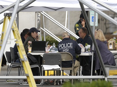 Law enforcement officials work under a tent, Saturday, Sept. 24, 2016, outside the Cascade Mall in Burlington, Wash. Authorities said Saturday several people were dead after the shooting Friday night and the suspect was still at large. The identity of the suspect, his motive and how he got a rifle into the mall remained unanswered. (AP Photo/Ted S. Warren)