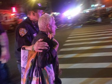 A police officer escorts an injured man away from the scene of a possible explosion on West 23rd Street in New York. AP