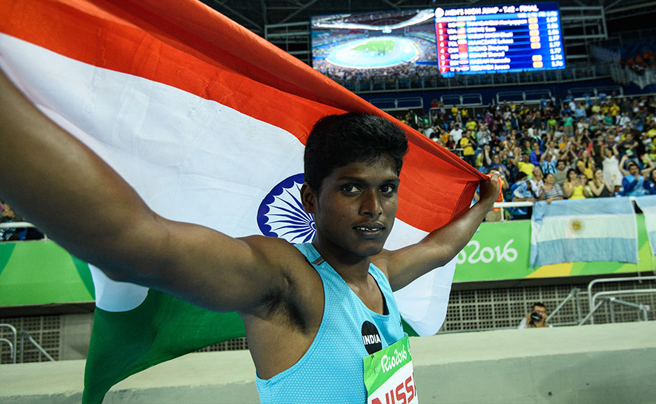 India's Mariyappan Thangavelu poses after winning the gold medal in the men's final high jump - T42 during the Paralympic Games at the Olympic Stadium in Rio de Janeiro on September 9, 2016. / AFP PHOTO / YASUYOSHI CHIBA